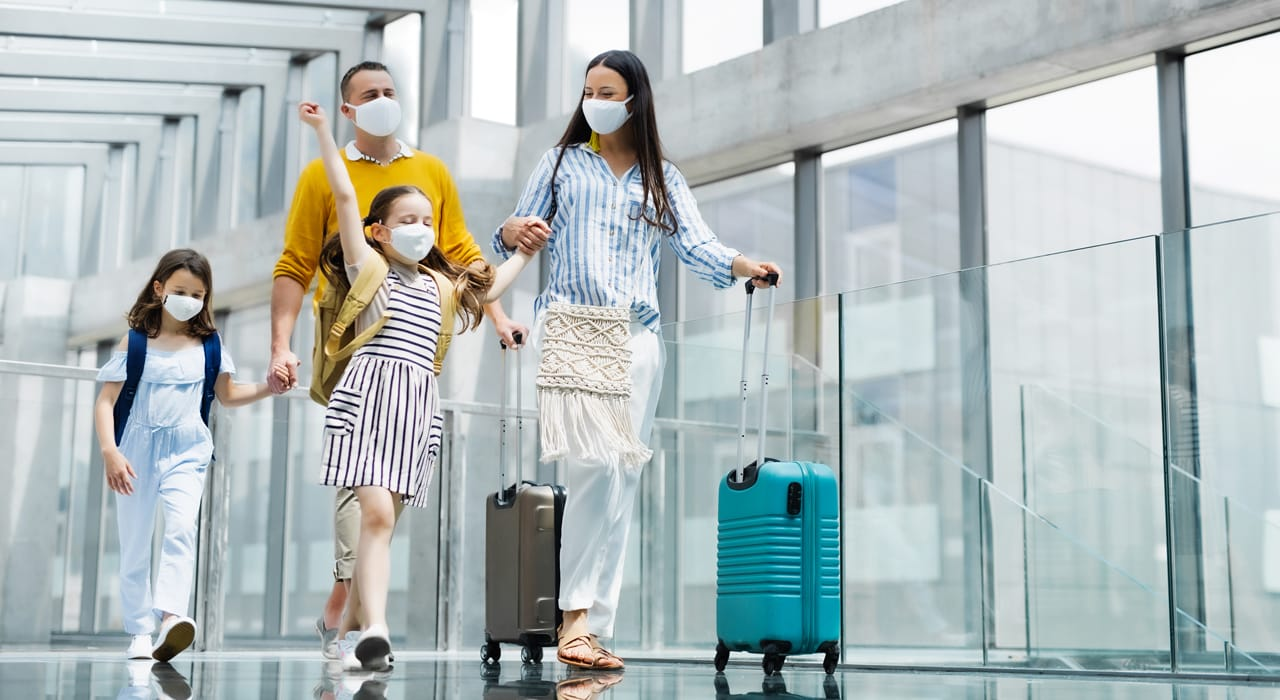 A family wear masks at the airport going on holiday during the pandemic